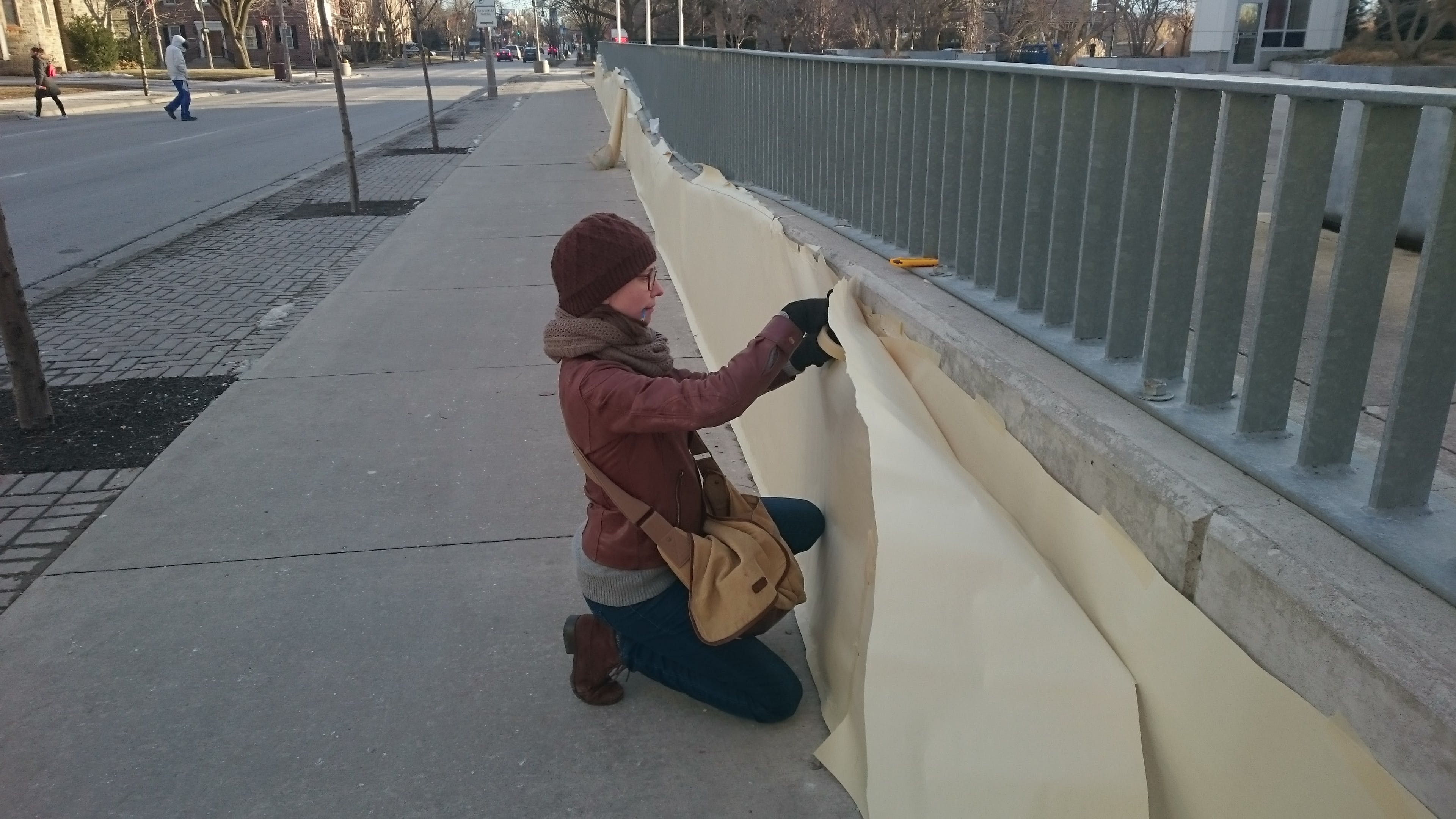 Durham College instructor creating the mural stencil