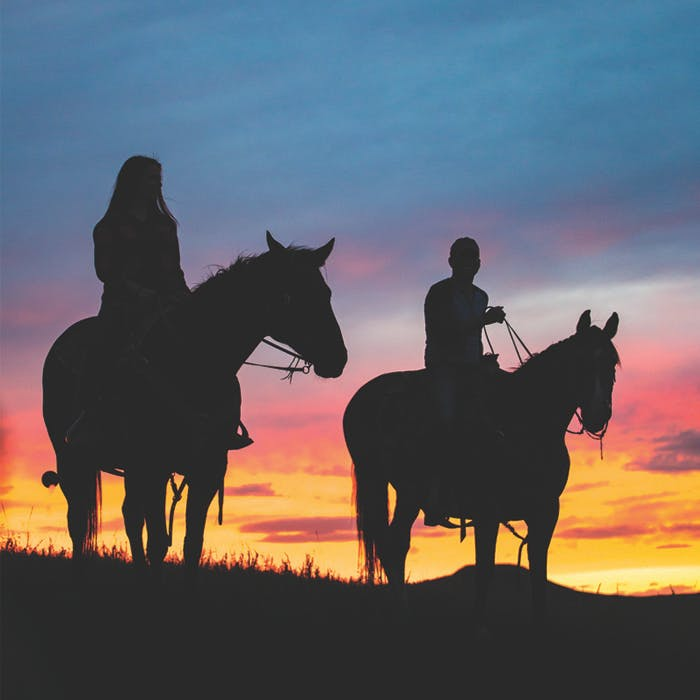 Silhouettes of two horseback riders at sunset