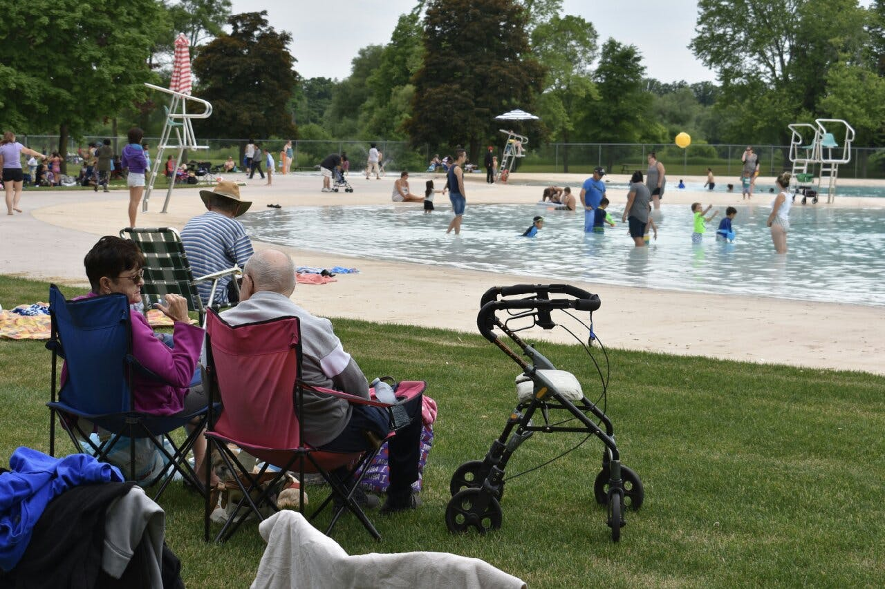 People sit in lawn chairs beside pool
