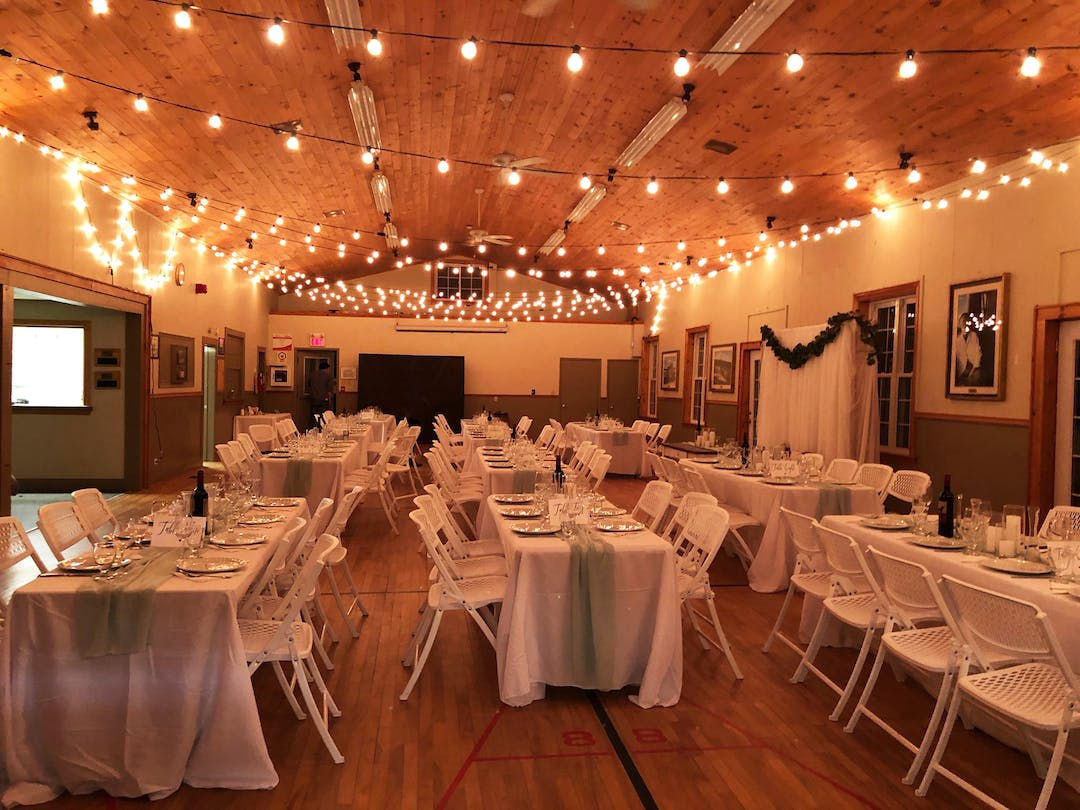 a hall filled with decorated wedding tables and hanging lights