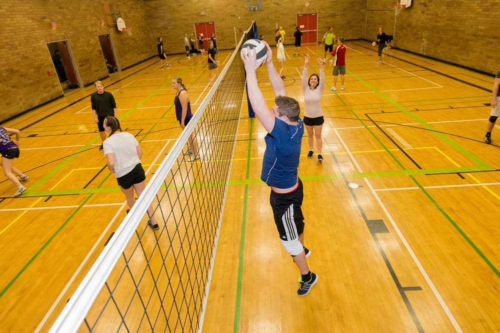 Inside a gym, young adults are playing volleyball