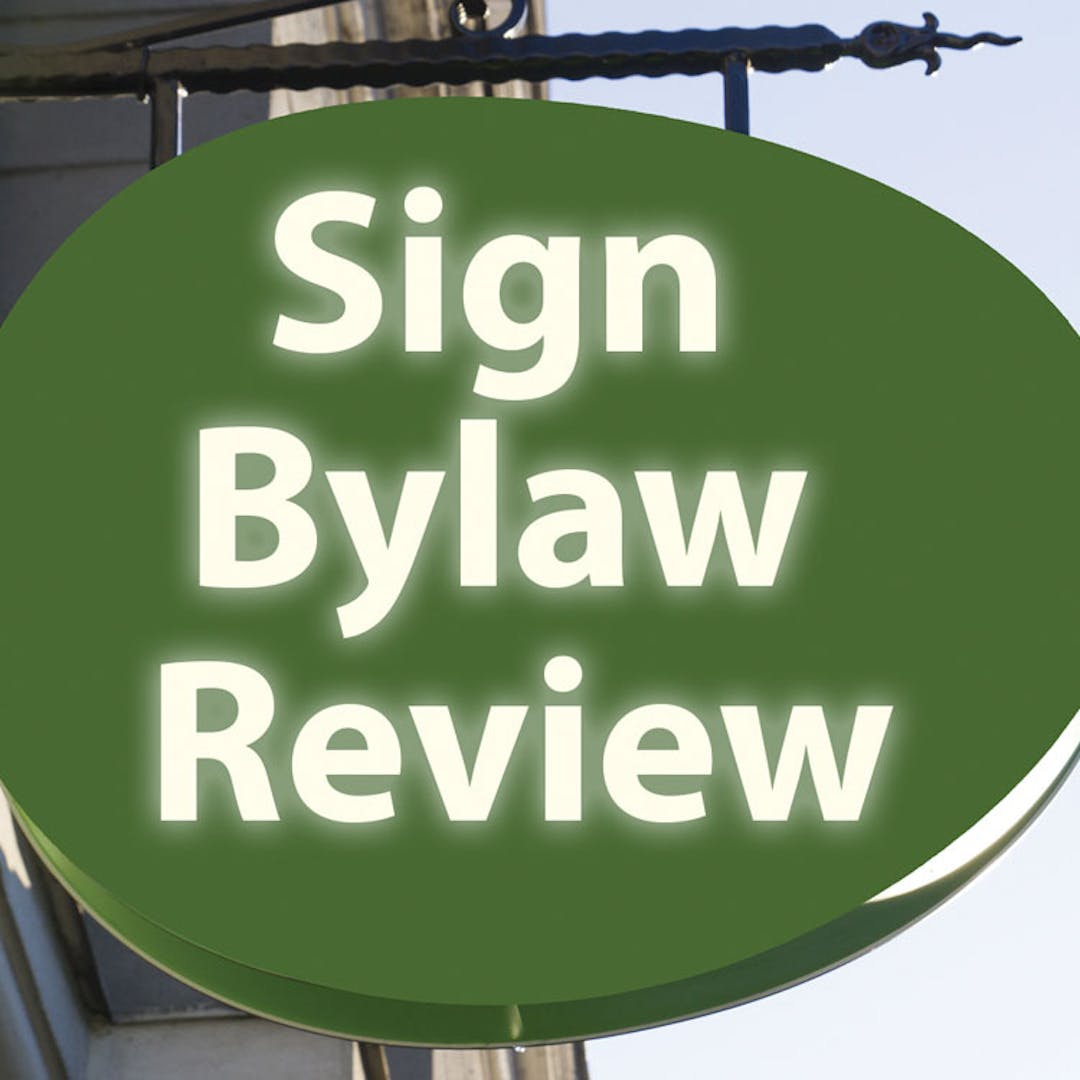 "Picture of a building sign with the words ""sign bylaw review""  printed on it"