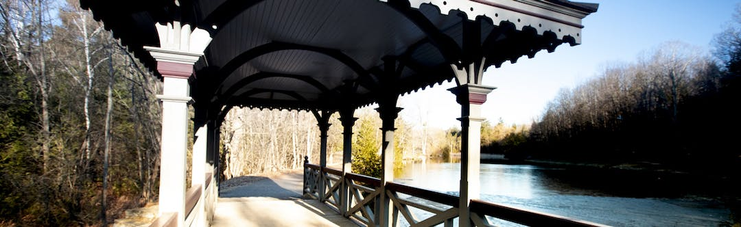 Covered pedestrian bridge in a park next to a pond
