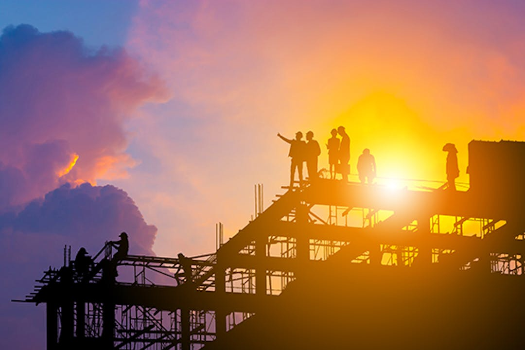 Construction workers standing on the top of a structure pointing into the sky at a faded Town of Midland logo during sunset.