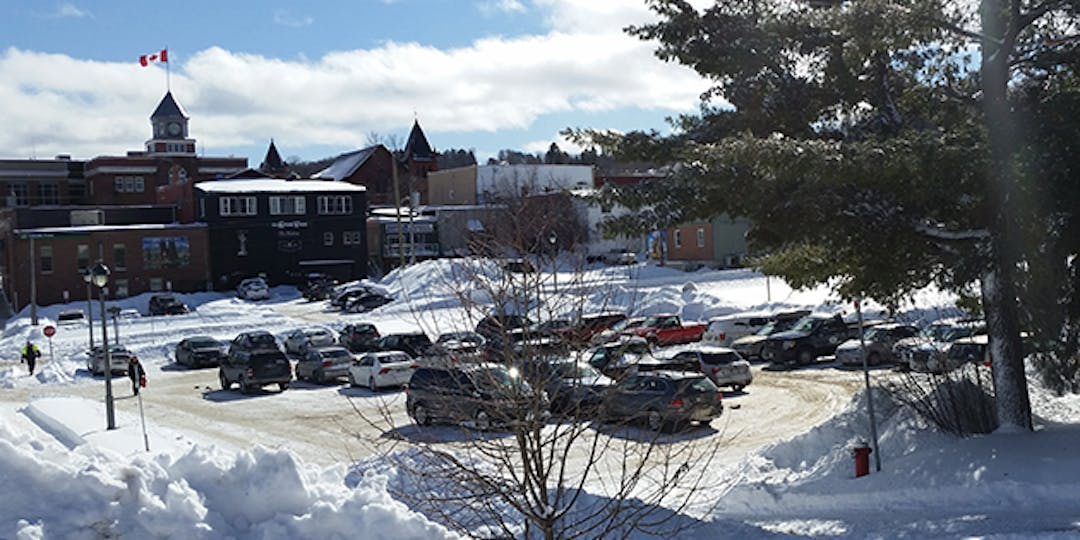 vehicles in a parking lot with town hall and Canada Flag in background