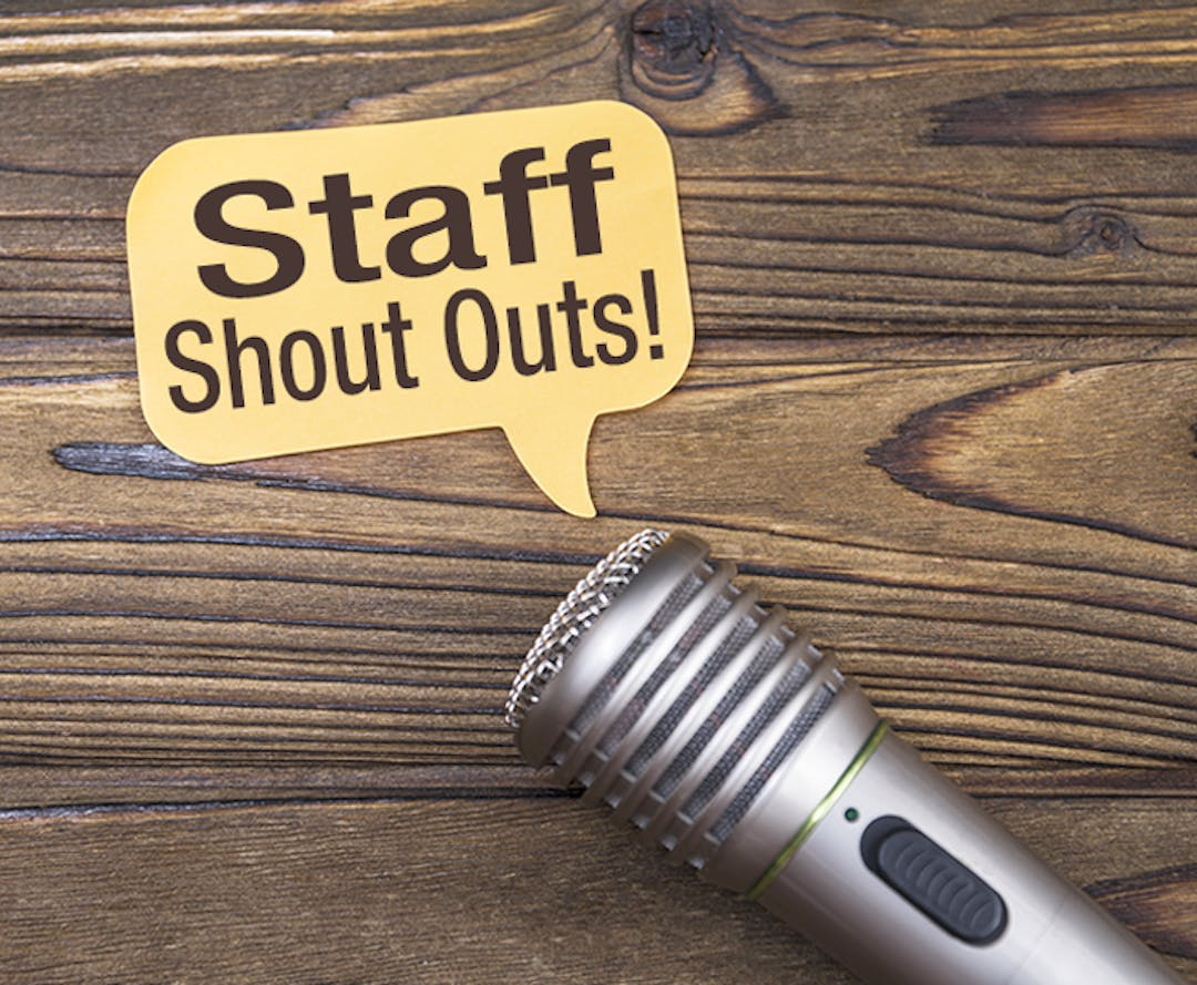"A photo of a microphone on a wood table, with a conversation window coming out of the end of the microphone that says ""Staff Shout Outs!"""