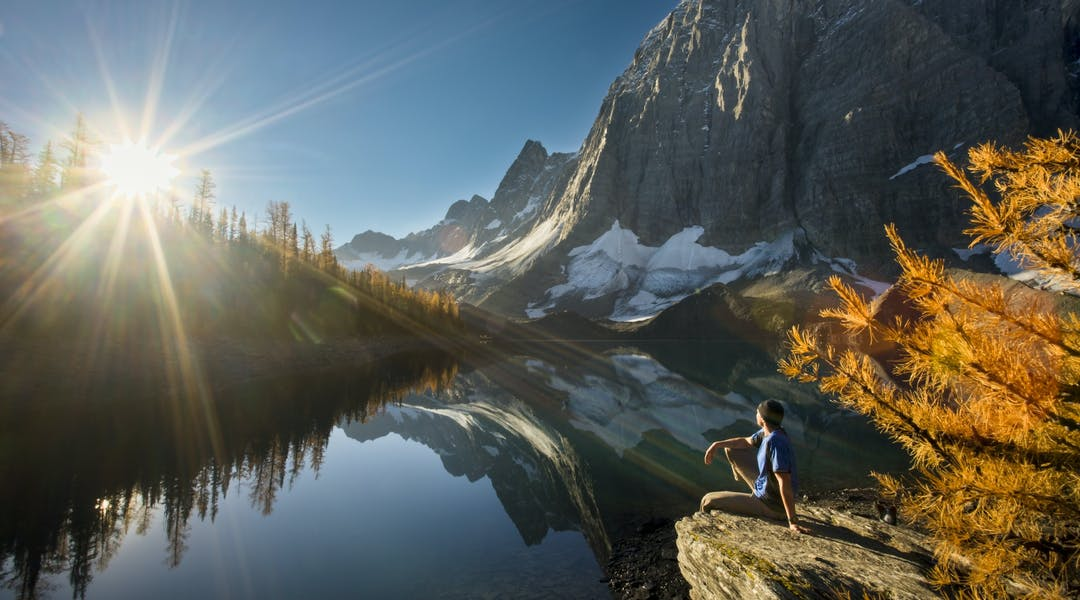Hiker overlooking lake during fall larch season on the Rockwall