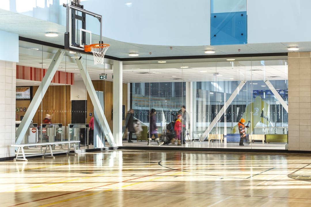 Image of indoor gymnasium with a view through the glass to the hallway in a recreation center