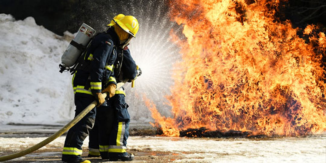 two firefighters water hosing a blaze