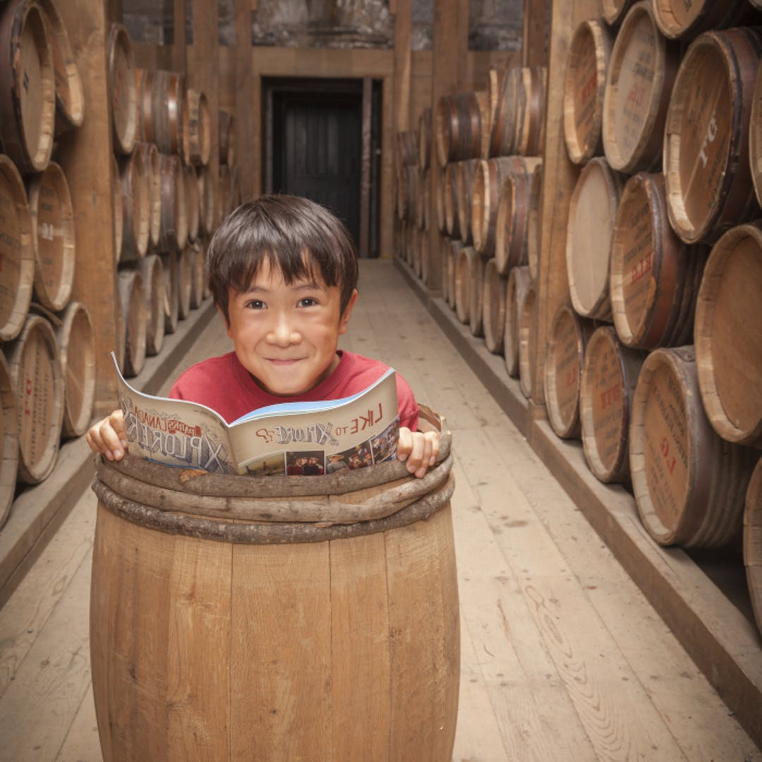 Young boy completes his Xplorer Guide in a barrel at the Halifax Citadel National Historic Site.