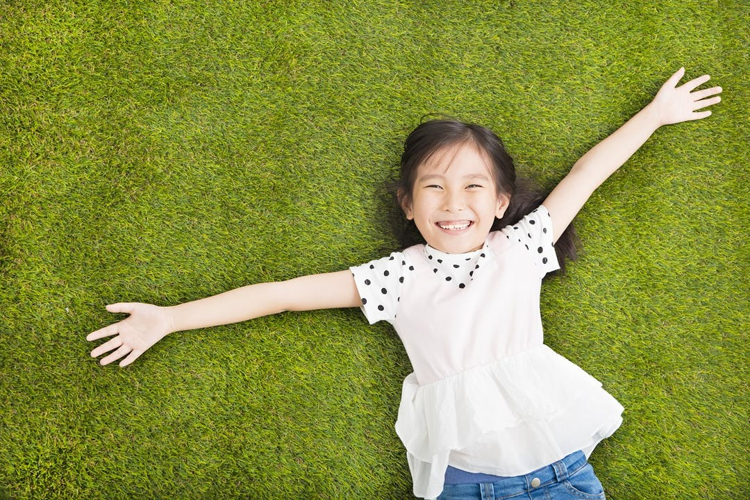 A happy girl lies with arms outstretched on the artificial turf