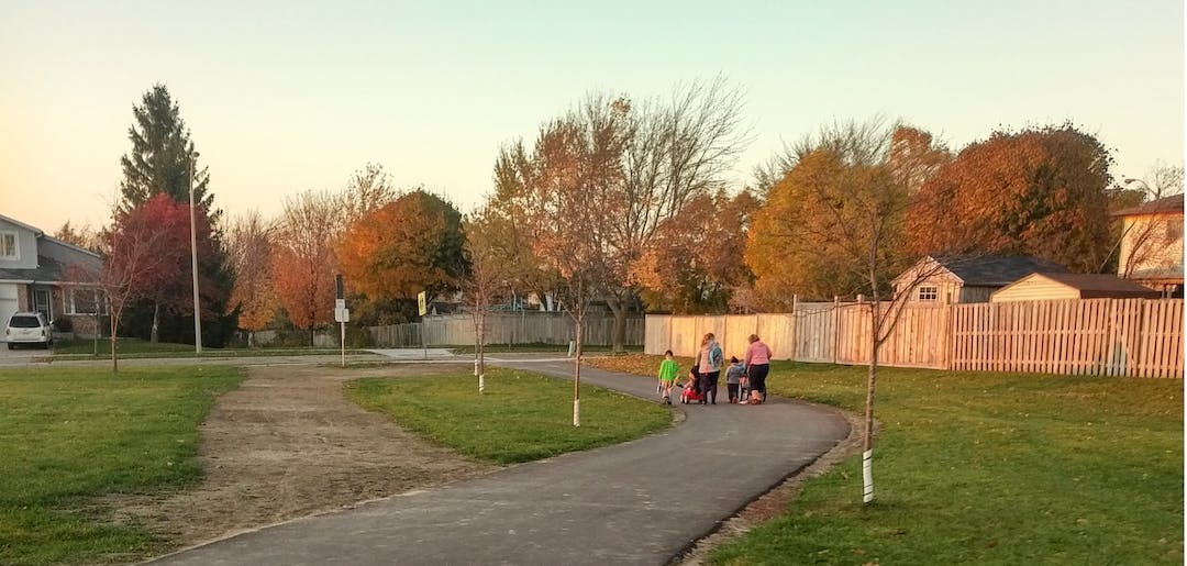 Children and adults walk up a paved trail running next to the old dirt path that leads away from the school.