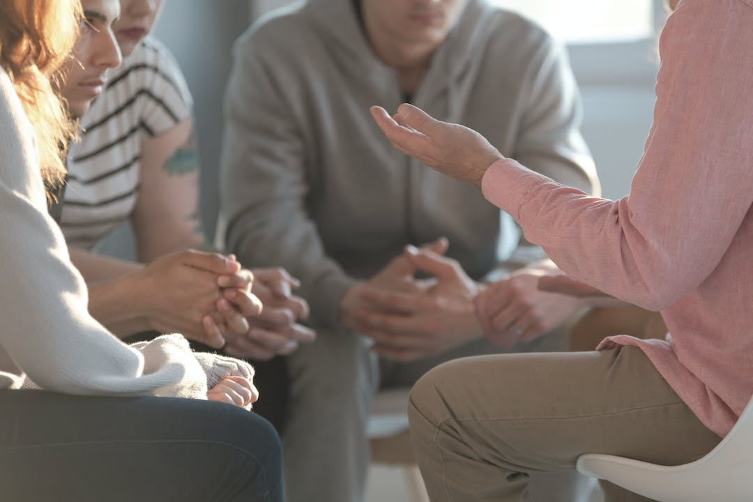 Close up of hands of a group leaning in close together in a circle engaged in conversation.