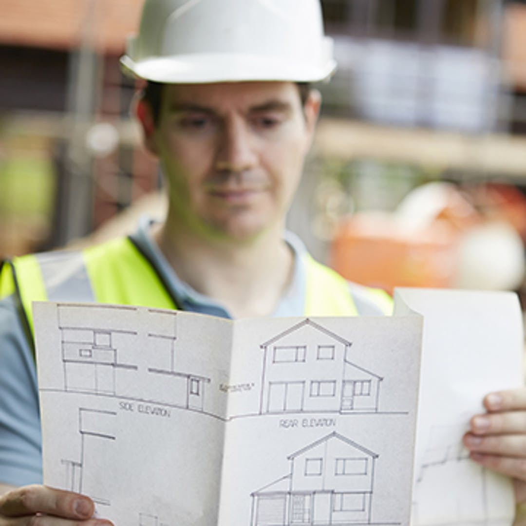 Building contractor in white hardhat in background examining home building plans in foreground.