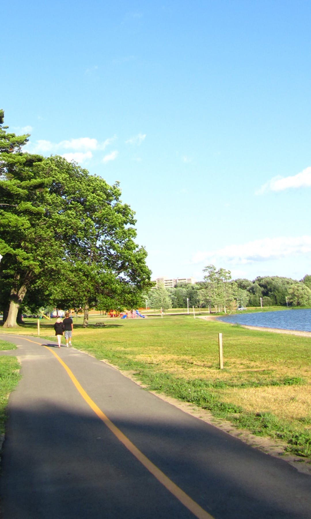A couple walking along a paved trail running through a park along the water. A playground can be seen in the distance.