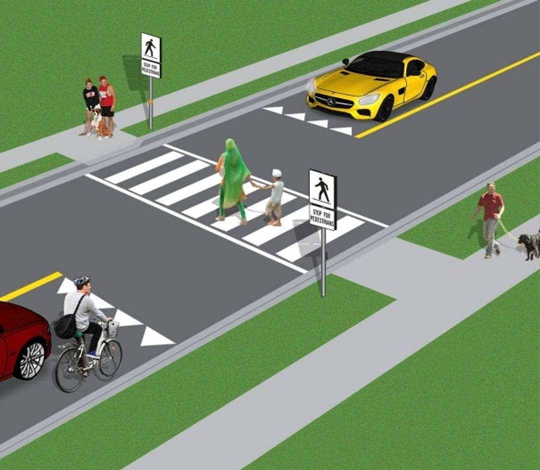 Pedestrian Crossover. Mother and son crossing the road. Two cars and a cyclist yielding for the pedestrians. People walking on the side walk.