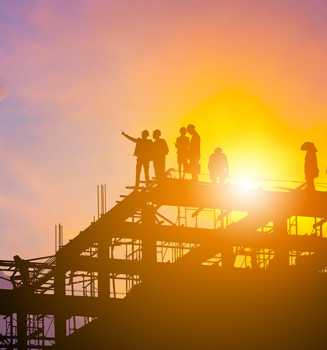 Construction workers standing on the top of a structure pointing into the sky during sunset.