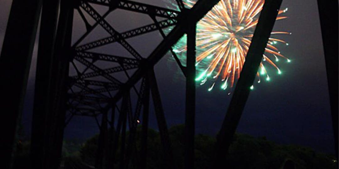 fireworks in the sky, photo taken underneath train bridge