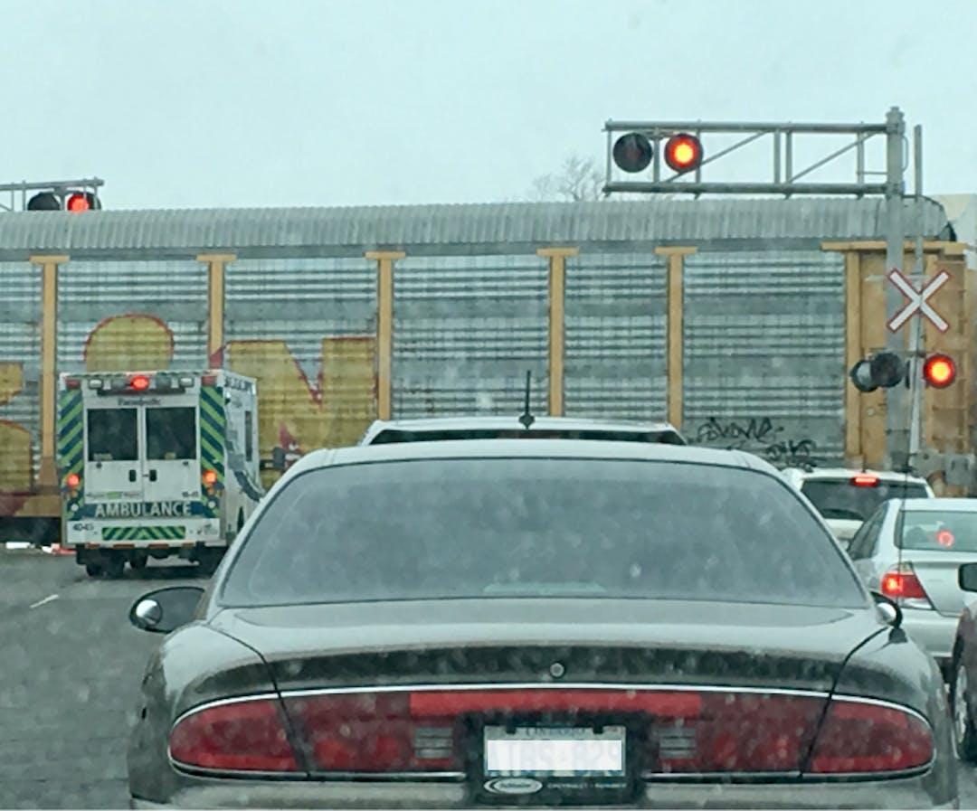 Cars waiting as a train passes through a crossing