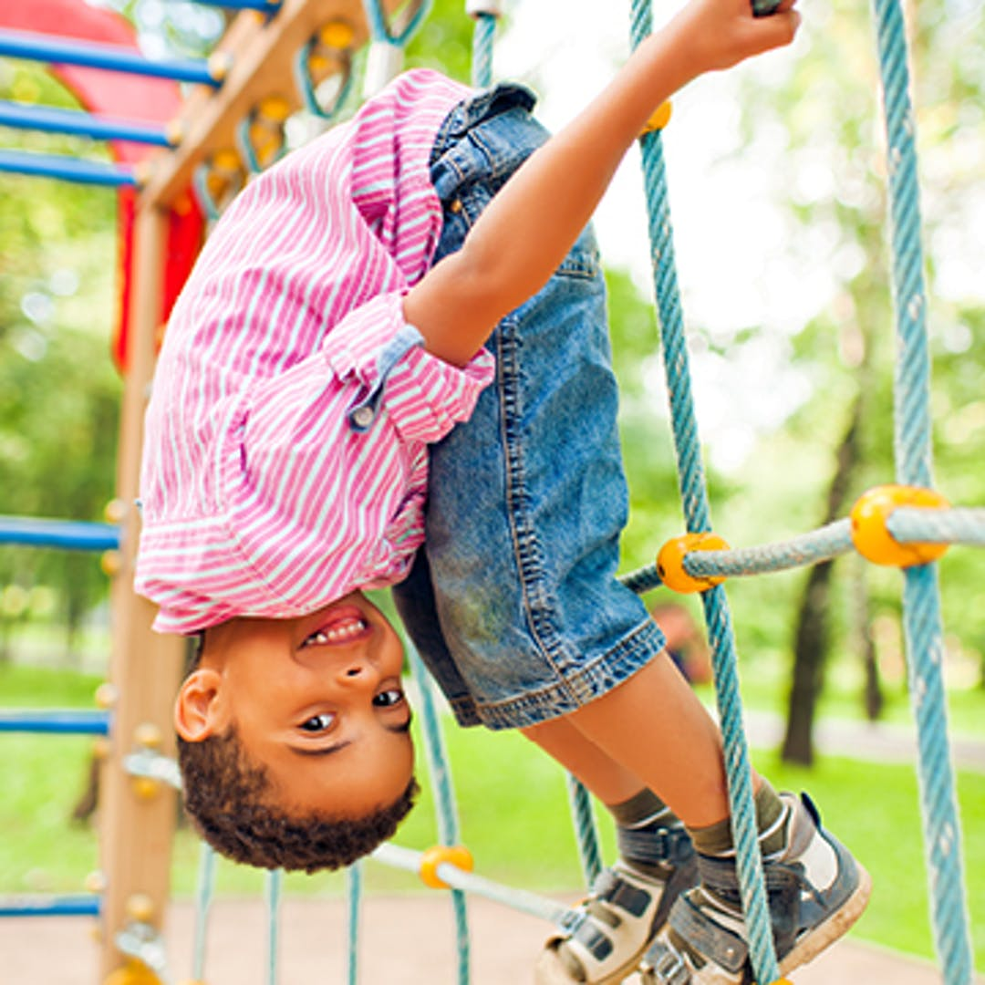 A young smiling boy hangs upside down on a playground climber.