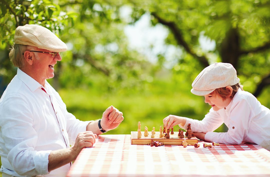 Senior gentleman and boy playing chess in the park