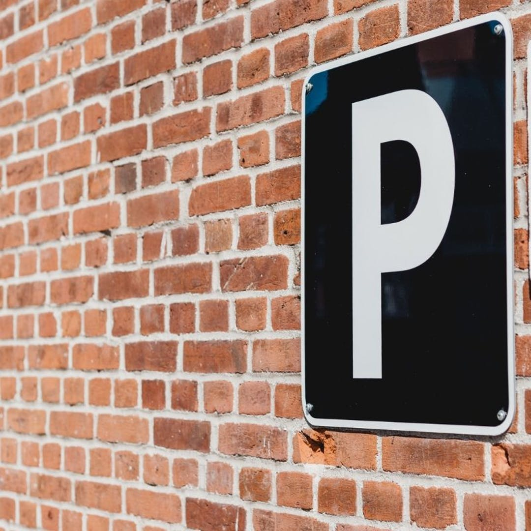Black and white parking sign on brick wall