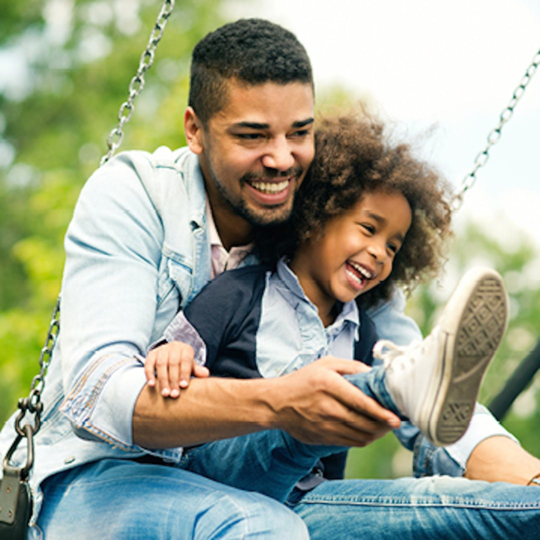 A man and a child swinging on a park swing and smiling.