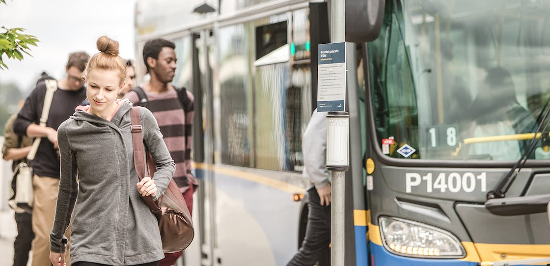 Photo of passengers disembarking at a bus stop.