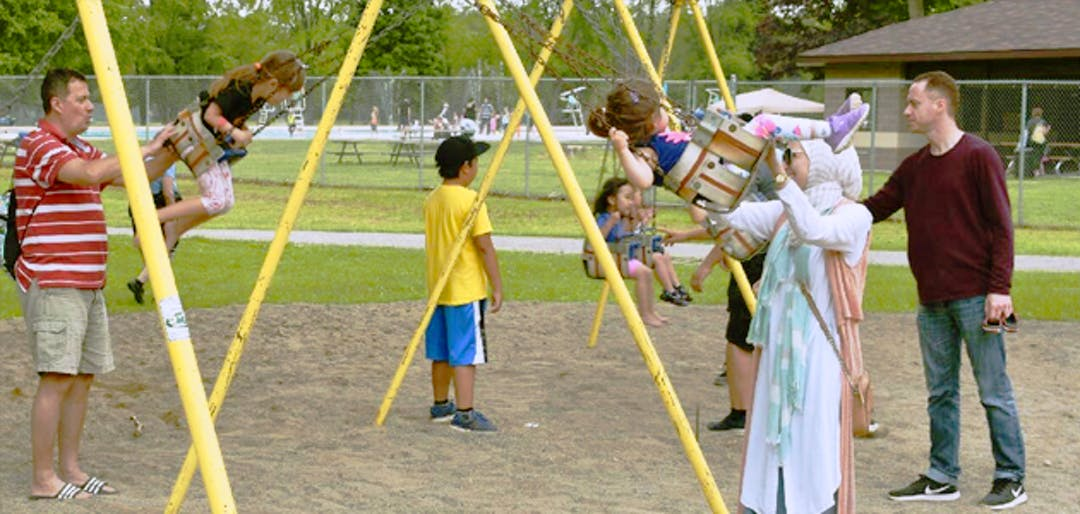 Adults push children on swings on the existing playground at Kiwanis Park.