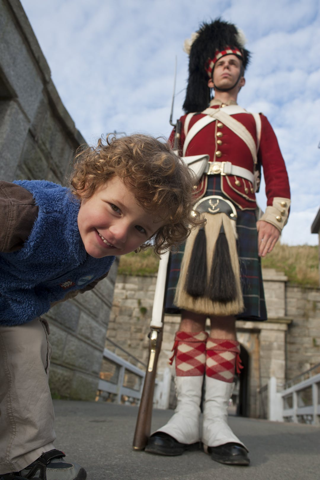 Interpreter portraying a 78th Highlander standing sentry at the front gate of the Halifax Citadel with a young boy checking things out.