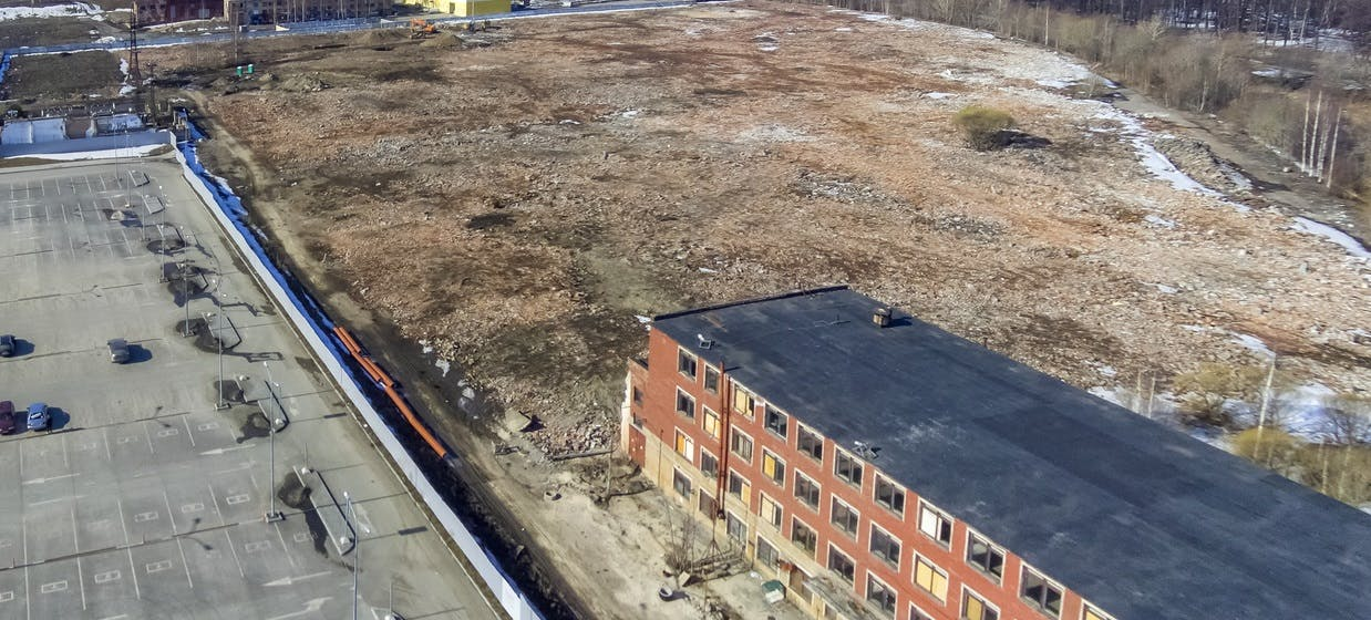 Areal photo of industrial building with adjacent vacant land. Land has not tress on it. There is a paved parking lot on one border of the land adjacent to the industrial building.