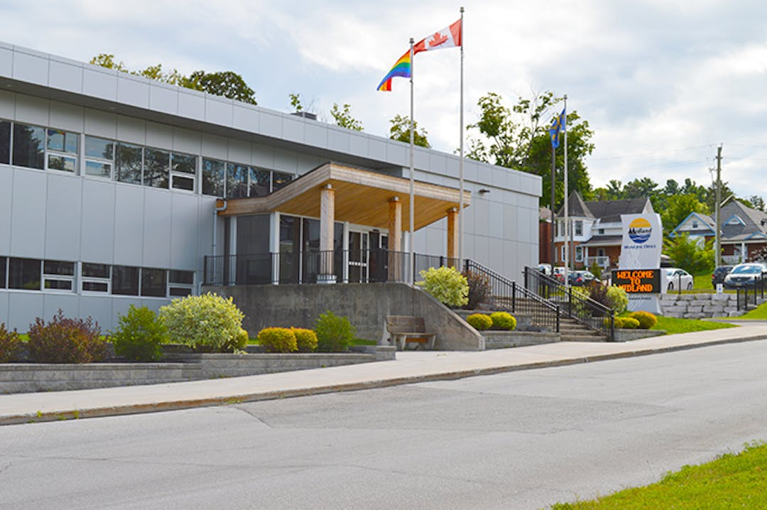 A photo of Midland Town Hall's Dominion Avenue entrance, showing the building, the digital sign with the Midland Logo above, and the flags blowing in the breeze.