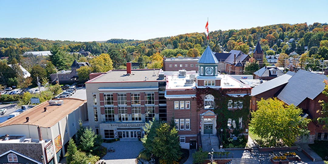 Aerial image of fall colours looking over the Huntsville Civic Centre, Algonquin Theatre and Town Hall municipal offices.