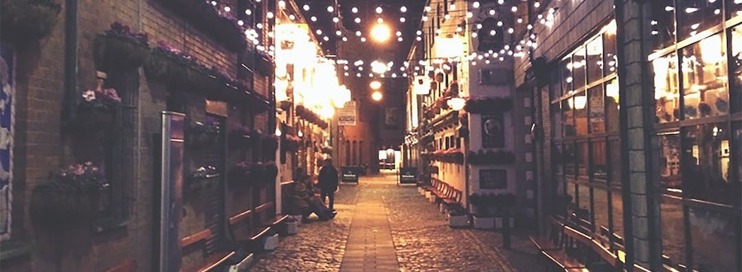 A laneway at night with lights strung across the sky providing light.