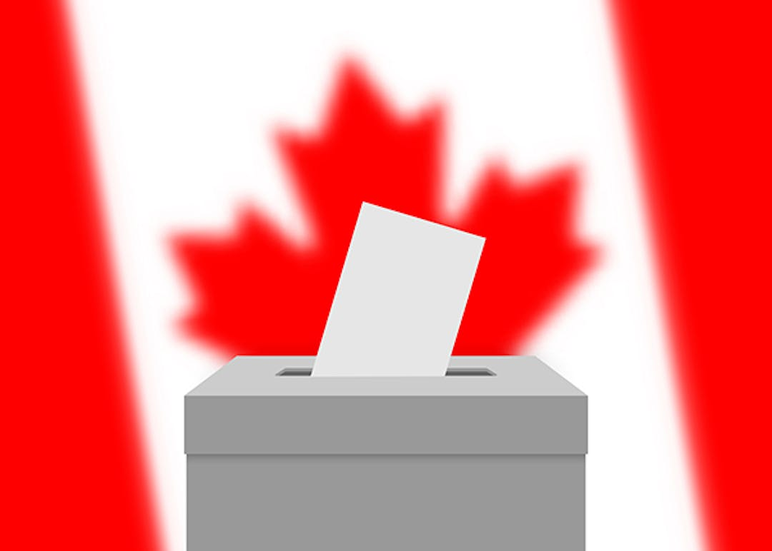 A ballot box with a ballot sticking out of the slot. The Canadian flag is in the background.